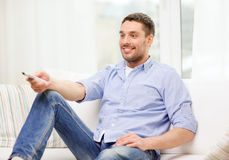 Smiling man with tv remote control at home. Home, technology and entretainment concept - smiling man with tv remote control at home royalty free stock photography