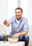 Smiling man with tv remote control at home. Home, technology and entretainment concept - smiling man with beer, popcorn and tv remote control at home stock photography