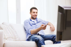 Smiling man with tv remote control at home. Home, technology, people and entertainment concept - smiling man with tv remote control at home stock photography
