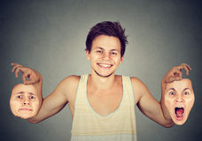 Smiling man with two different emotion masks Stock Photography