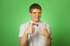 Smiling Man two thumbs up. Handsome young man in a shirt and yellow glasses, bow tie on a green background smiling at the camera. Two thumbs up Stock Image