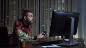 Smiling man typing on computer. Cheerful bearded man in office smiling and typing on computer at night stock footage
