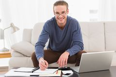 Smiling man using calculator counting his bills Royalty Free Stock Image