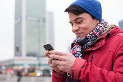 Smiling man using cell phone in city during winter Royalty Free Stock Images