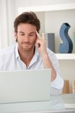 Smiling man using computer at home Stock Images