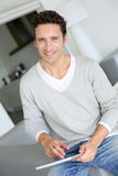 Smiling man using digital tablet at home Stock Image