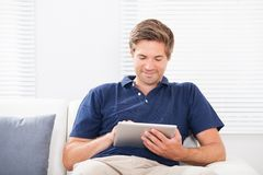 Smiling man using digital tablet on sofa Royalty Free Stock Photo