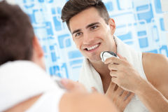 Smiling man using electric shaver. Smiling young man using electric shaver front of mirror Stock Photography