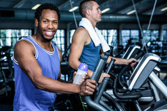 Smiling man using elliptical machine royalty free stock photos