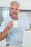 Smiling man using his laptop while having coffee Royalty Free Stock Photo