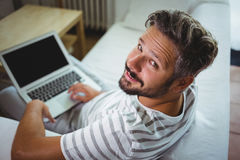 Smiling man using his laptop in living room Royalty Free Stock Images