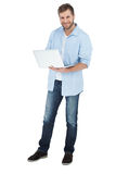 Smiling man using his laptop looking at camera. On white background Royalty Free Stock Photo