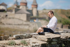 Smiling man using his laptop outside Royalty Free Stock Photo