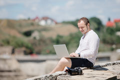 Smiling man using his laptop outside Stock Photos