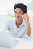 Smiling man using his laptop and talking on phone Royalty Free Stock Photos