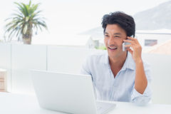 Smiling man using his laptop and talking on phone. Outside on a balcony Royalty Free Stock Photography