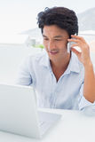 Smiling man using his laptop and talking on phone. Outside on a balcony Royalty Free Stock Photos