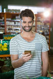 Smiling man using his phone in the organic section Royalty Free Stock Photography