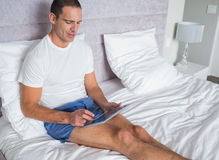 Smiling man using his tablet pc on bed Stock Images