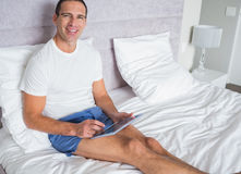 Smiling man using his tablet pc sitting on bed Stock Photo