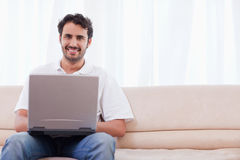 Smiling man using a laptop Royalty Free Stock Images