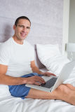 Smiling man using laptop on bed Stock Photos