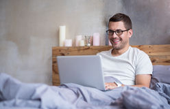 Smiling man using laptop in a bed Royalty Free Stock Photography