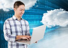 Smiling man using laptop with clouds and binary codes in background Royalty Free Stock Photo