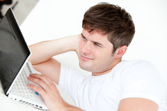 Smiling man using a laptop lying on his bed Royalty Free Stock Photography