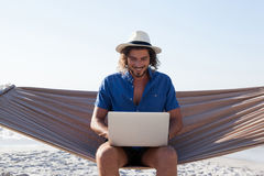 Smiling Man using laptop while sitting on hammock at beach. During sunny day Royalty Free Stock Photos