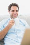 Smiling man using laptop sitting on sofa having a coffee Royalty Free Stock Image