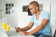 Smiling man using laptop and smartphone Stock Photos