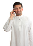 Smiling man using phone. Smiling ethnic business man using a mobile phone and in traditional ethnic robe - Kurta - fastened with ruby buttons. The name Kurta is Stock Photo
