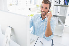 Smiling man using phone and computer in office Stock Photo