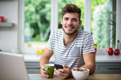 Smiling man using phone while having coffee Stock Images