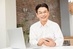 Smiling man using smartphone and laptop Stock Photo