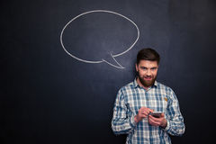 Smiling man using smartphone over blackboard background with speech bubble. Smiling young man using smartphone over blackboard background with empty speech Royalty Free Stock Photos