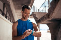 Athlete checking his progress on smartwatch fitness app. Smiling man using a smartwatch to monitor his progress. Male athlete checking his performance on fitness stock photos