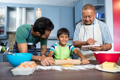 Smiling man using table while standing by father and son preparing food. Smiling men using table while standing by father and son preparing food in kitchen at Royalty Free Stock Photo