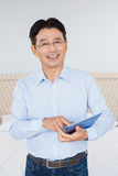 Smiling man using tablet. In bedroom Stock Photography