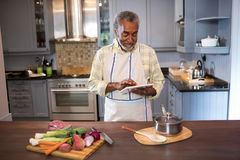 Smiling man using tablet computer while cooking food. In kitchen at home Stock Image