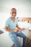 Smiling man using tablet in the kitchen Royalty Free Stock Image