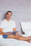 Smiling man using tablet pc on bed Royalty Free Stock Image