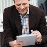 Smiling man using a tablet-pc. Closeup of a smiling young business man sitting using a tablet-pc scrolling with his finger on the touchscreen Stock Images