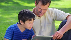 Smiling man using a tablet pc with his son. In a parkland stock video footage