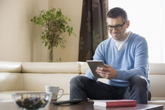 Smiling man using tablet PC at home Stock Photos