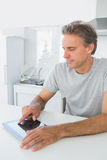 Smiling man using tablet pc in kitchen Stock Images
