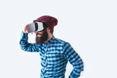 Smiling man using VR headset. Young bearded male in checkered shirt and hat laughing while using VR headset on white background Stock Photography