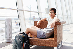 Smiling man waiting for flight at airport. Happy young man in glasses and headphones sitting on chair in airport departure lounge Royalty Free Stock Photos