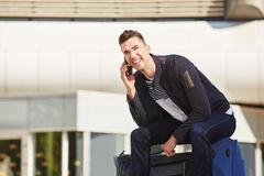 Smiling man waiting at station with luggage on phone call Stock Photos